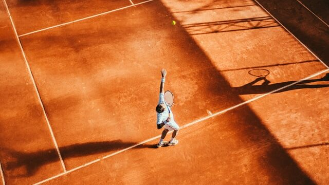 Tennis player making a service on gravel